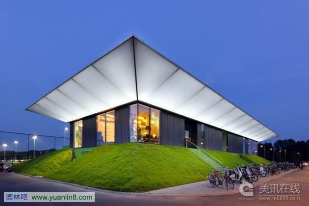 MoederscheimMoonen Architects建筑事务所最近为荷兰鹿特丹两个足球俱乐部设计了一座新的足球馆。这个足球馆建造在郊区地带,位于市中心和机场之间。考虑到附近的机场和新建的公园房屋,建筑师设计出一个透明、轻型的场馆。   建筑共有两层。俱乐部会所和会议室位于顶层。更衣室和储藏室位于下层。   建筑采用透明的悬伸屋顶设计。这种屋顶在白天能过滤直射光,到了晚上就像是一个灯笼。   流线型的建筑轮廓和灯光屋顶使得整个建筑非常有特色。